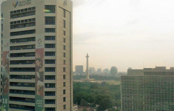 Monumen Nasional (Monas) terlihat di kejauhan dari gedung bertingkat di Jakarta