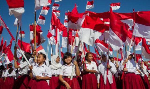 Anak-anak sekolah dasar memegang bendera Indonesia