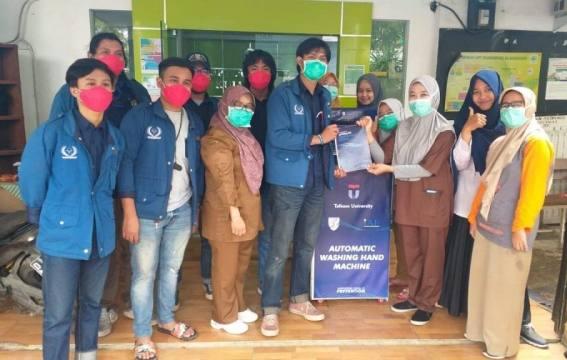 Mahasiswa Telkom University menyerahkan bantuan alat cuci tangan otomatis. (kalderanews.com/Dok.Telkom University)