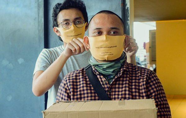 VP of Operations Sampingan Ryan Dwi Putra (kiri) memakaikan masker kepada salah satu Kawan Sampingan di Jakarta