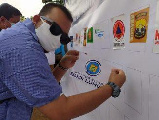 Humas Universitas Budi Luhur menempelkan logo Universitas Budi Luhur dalam Deklarasi Komitmen Dukungan Pentahelix dalam Penanganan Covid-19 di TPU Pondok Rangon yang diinisiasi oleh Badan Nasional Penanggulangan Bencana (BNPB) pada Minggu, 16 Agustus 2020