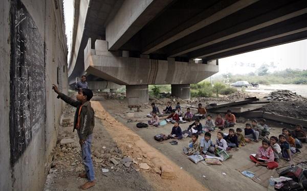 Guru mengajar anak-anak miskin di bawah jembatan di New Delhi