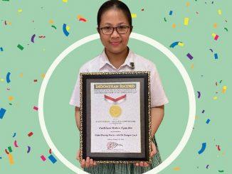 """Cathleen Mulan Tyas Ho, salah satu murid SD Santa Ursula Jakarta, dengan piagam penghargaan MURI sebagai """"Pelatihan Menggambar Edukatif Secara Daring oleh Pelatih Termuda"""""""