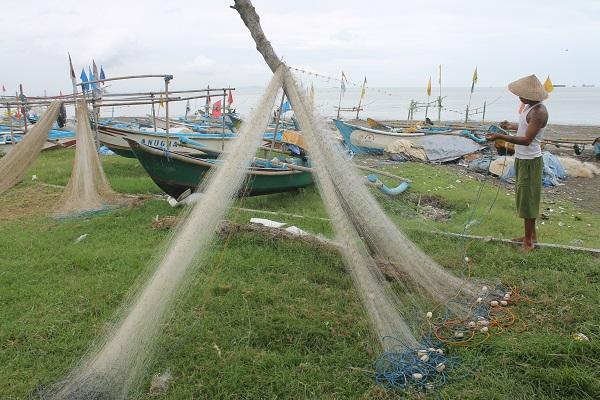 Nelayan di tepi Pantai Teluk Penyu Cilacap