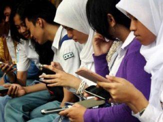 Siswa SMA dengan smartphone di tangan