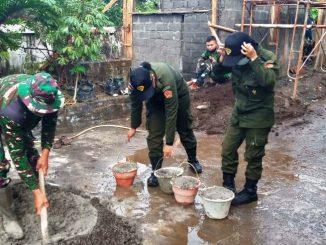 Dua mahasiswi UTY sedang membantu mencampur semen untuk pembangunan pos RW
